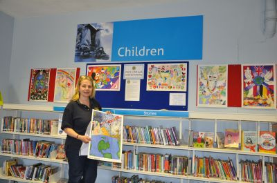 Lion Theresa pictured at Cheddar Library with Posters entered into the International Peace Poster Competition by pupils from Hugh Sexey Middle School