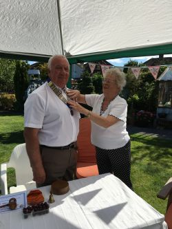 Lion Keith receiving the President's Chain from Lion Marion